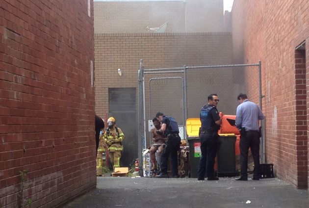 Police speak with a man out the back of the Commonwealth bank branch on