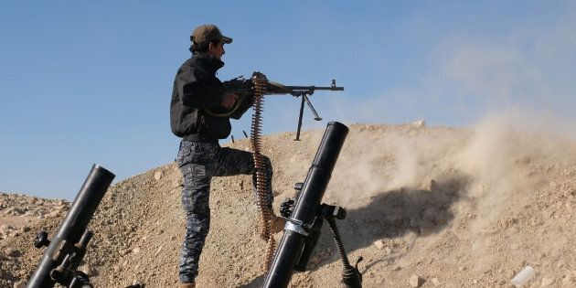 A member of the Iraqi Federal Police fires his weapon at an Islamic State (IS) group target on the front...