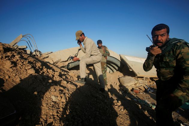 Members of the Shi'ite Badr Organisation fighters take cover behind a berm during a battle with Islamic...