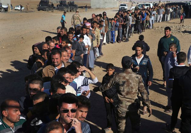 Mosul residents wait in a queue to receive food supplies, at the city's al-Samah neighbourhood on Nov....