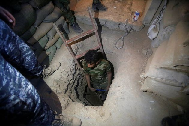 A member of the Shi'ite Badr Organisation fighter inspects a tunnel used by Islamic State militants during...