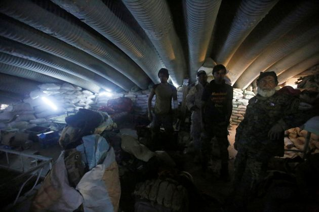 Members of the Shi'ite Badr Organisation fighters inspect a tunnel used by Islamic State militants during...
