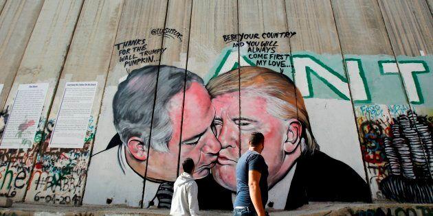 Palestinian men walk past a graffiti by street artist Lushsux.