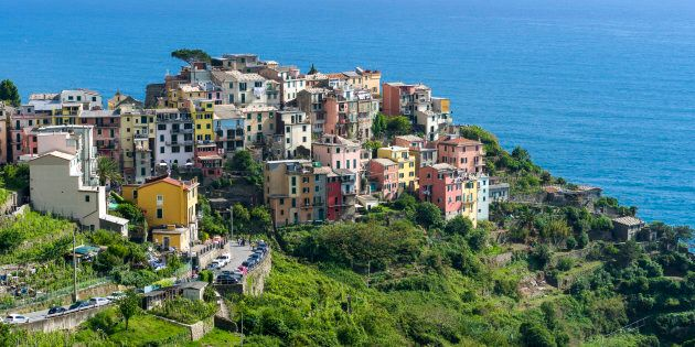 The colorful houses of Corniglia town, part of Cinque Terre, are crammed on a hill on the cost of the...
