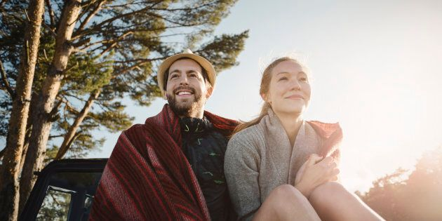 Happy wonderlust couple wrapped in blanket sitting on jeep against clear sky