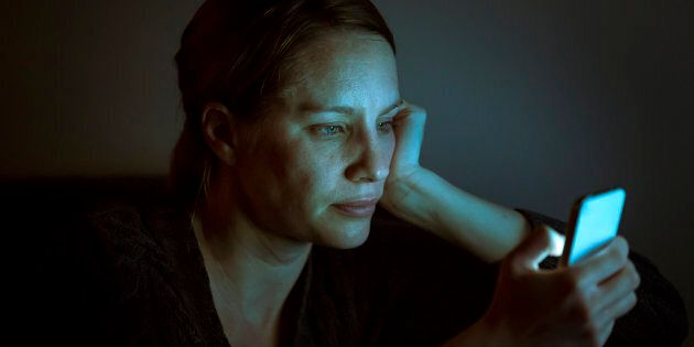 A woman illuminated by the glow of her smart phone at night