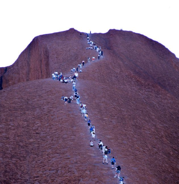 Hundreds of people continue to climb Uluru, despite signs asking people not to climb out of respect for...