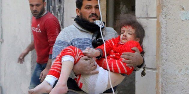 ALEPPO, SYRIA - NOVEMBER 22: A resident carries a wounded child girl pulled out of a debris after the...