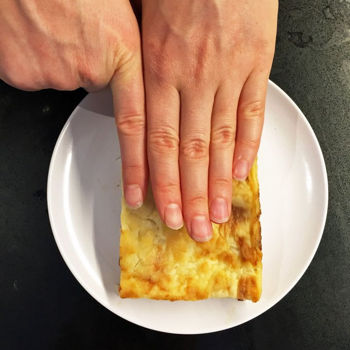 The finger width method in action to measure a slice of lasagna.