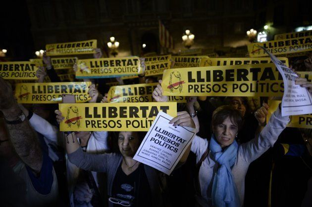 Protesters hold signs reading 'Freedom to political prisoners' during a demonstration in