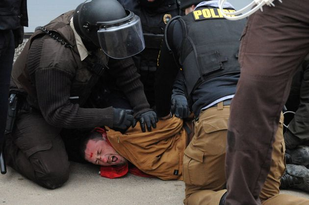 A protester is detained by police in Bismarck during a
