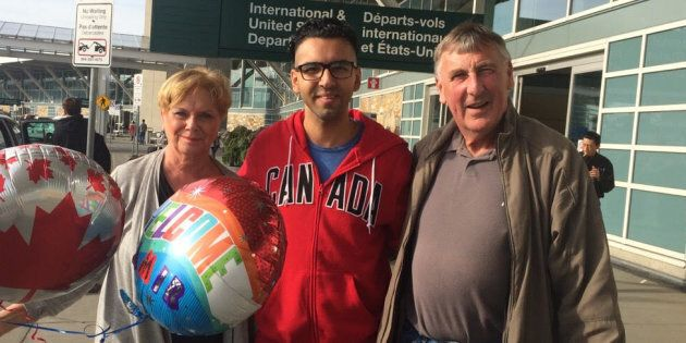 Amir (centre) with Wayne and Linda Taylor, after arriving in