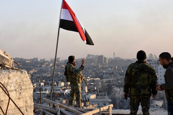 A Syrian government soldier gestures a v-sign under the Syrian national flag near a general view of eastern Aleppo after they took control of al-Sakhour neigbourhood in Aleppo.