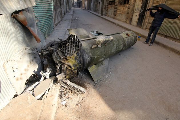 A man inspects an unexploded missile in the rebel-held besieged al-Qaterji neighbourhood of Aleppo, Syria...