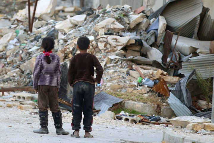 Children inspect rubble of damaged buildings in a rebel-held besieged area in Aleppo