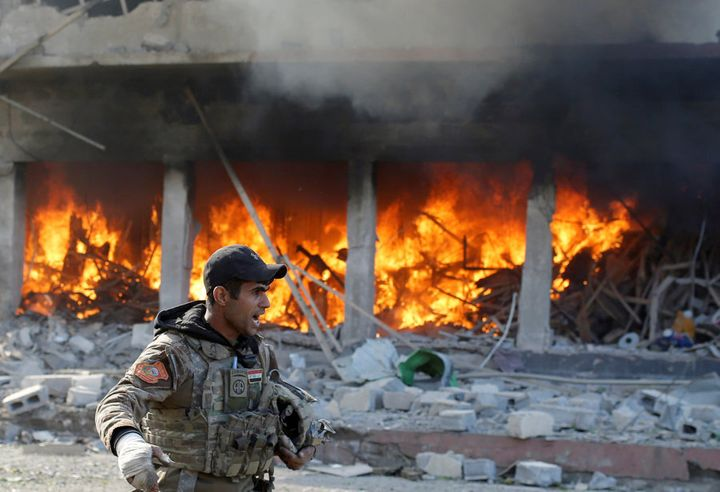 An Iraqi special forces soldier shouts in front of a burning house after an Islamic State suicide car bomb attack against Iraqi special forces during clashes in Mosul, Iraq, November 19, 2016