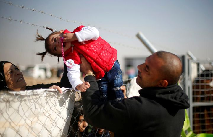 A displaced Iraqi man, who fled the Islamic State stronghold of Mosul, holds his daughter to be seen by her grandmother through a fence at Khazer camp, Iraq November 28, 2016.