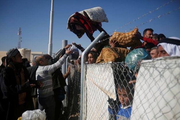 Displaced Iraqis (L), who fled the Islamic State stronghold of Mosul, throw aid supplies from inside...