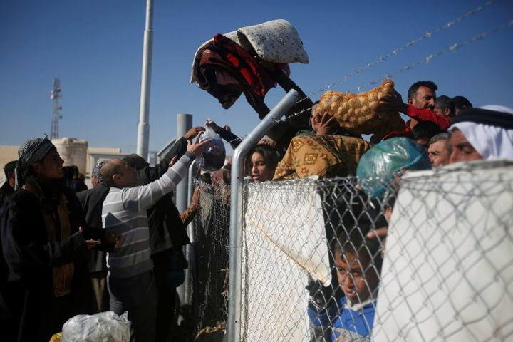 Displaced Iraqis (L), who fled the Islamic State stronghold of Mosul, throw aid supplies from inside Khazer camp to their displaced relatives who are waiting for permission to enter the camp, in Iraq November 26, 2016
