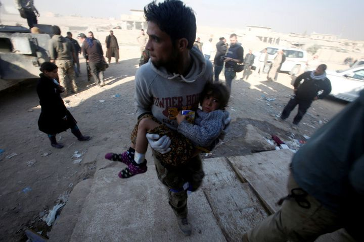 A member of Iraqi special forces carries an injured girl from clashes in Mosul, Iraq, November 29, 2016