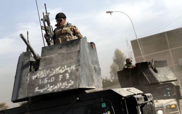 An Iraqi special forces member holds a position in an armoured vehicle in a recently recaptured district...
