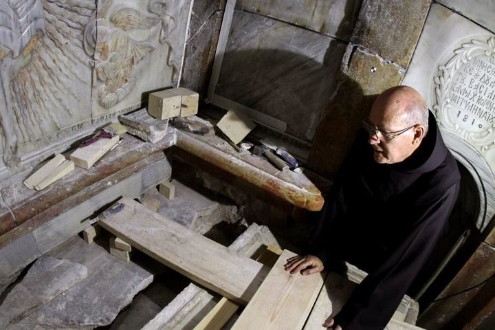 A Franciscan friar looks at the exposed the Tomb of Jesus, where his body is believed to have been laid, as part of conservation work done by a team of Greek team of preservation experts in Jerusalem on late on October 28, 2016.
