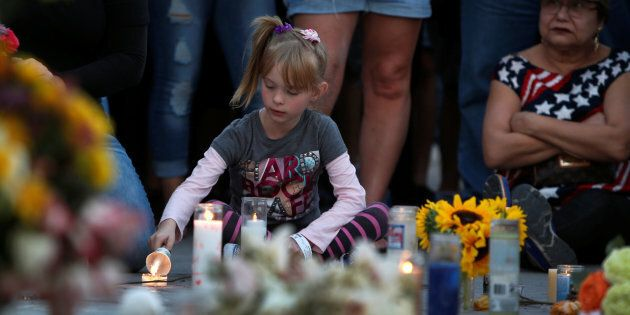 A girl lights a candle at a makeshift memorial during a vigil marking the one-week anniversary of the October 1 mass shooting in Las Vegas, Nevada U.S. October 8, 2017.