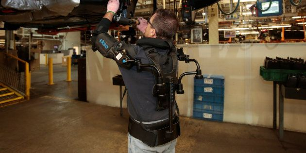 Ford assembly worker Paul Collins wears an EksoVest as he works on the assembly line producing the Ford...