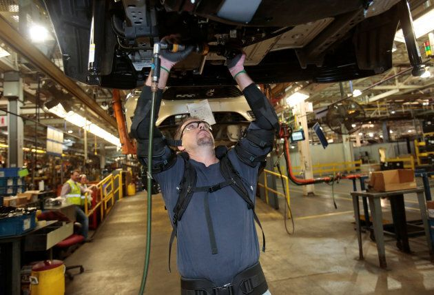 Ford Motor Co assembly worker Paul Collins wears an EksoVest as he works on the assembly