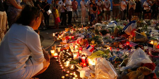 A man reacts near the scene where a truck ran into a crowd at high speed killing scores and injuring more who were celebrating the Bastille Day national holiday, in Nice, France on Thursday.