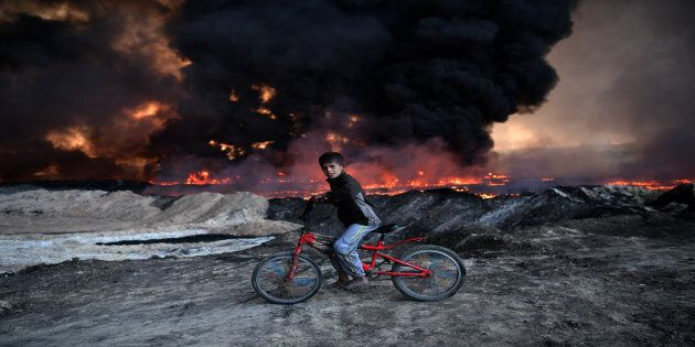 A boy pauses on his bike as he passes an oil field set alight by retreating ISIS fighters ahead of the...