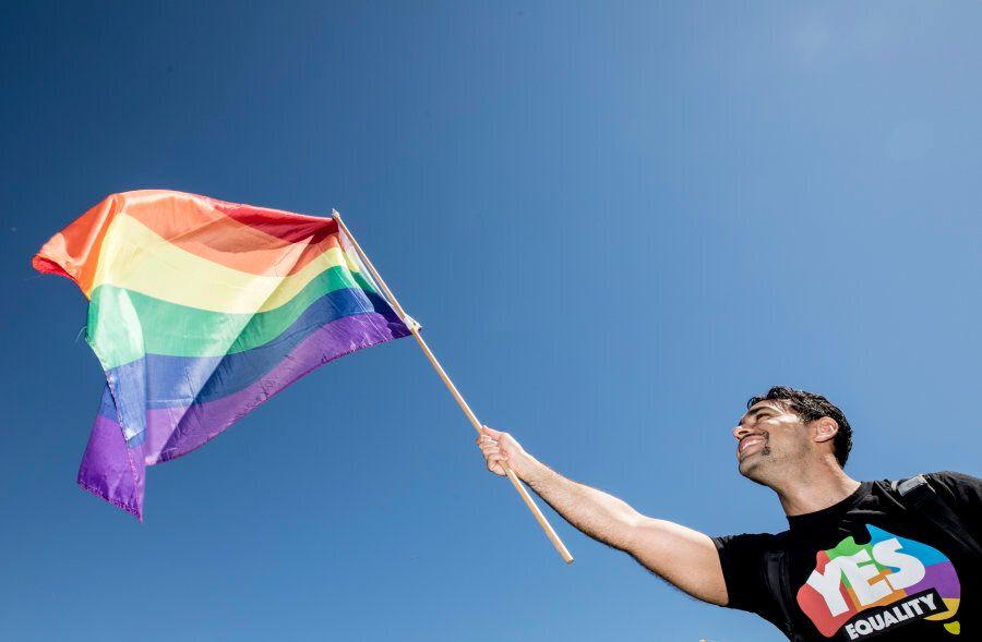 Sydney, Australia -- November 15: A man proudly waves the LGBTQ Pride