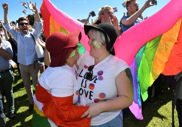 A couple embrace as supporters of the same-sex marriage 'Yes' vote celebrate the announcement in a Sydney park on November 15, 2017.