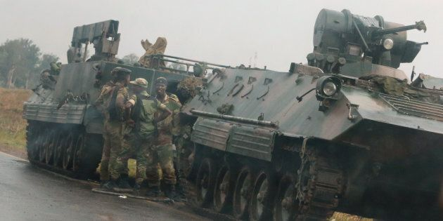 Soldiers stand beside military vehicles just outside Harare, Zimbabwe, on November 14,