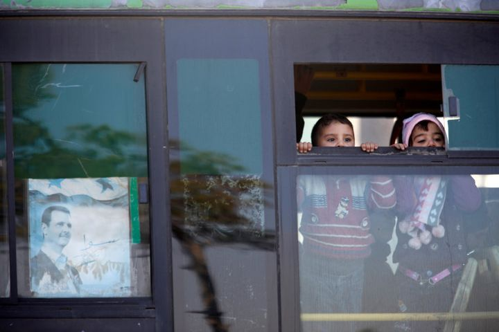"""Children who came back with their families to inspect their homes, ride a bus in goverment controlled Hanono housing district in Aleppo, Syria December 4, 2016. The poster shows Syria's president Bashar al-Assad and reads in Arabic """"Together""""."""