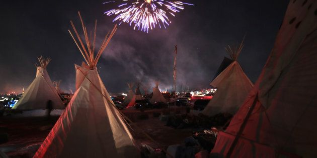Fireworks fill the night sky above Oceti Sakowin Camp as activists celebrate after learning an easement...