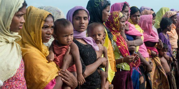 Women hold children at a makeshift camp in Rakhine state in