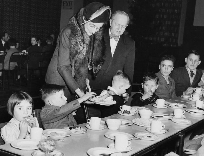 Noel W Lamidey with Lady Harrison, and migrant children at Australian House, 1950.