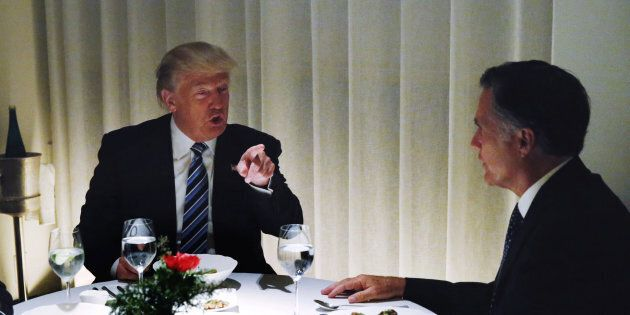 U.S. President-elect Donald Trump sits at a table for dinner with former Massachusetts Governor Mitt...