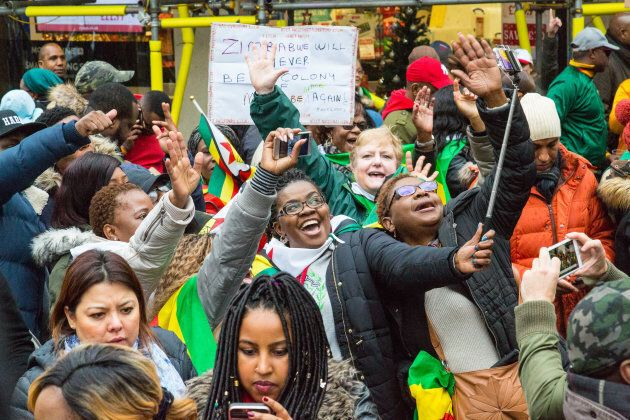 Exiled Zimbabweans of all races gather outside the Zimbabwe Embassy in London to celebrate the military...