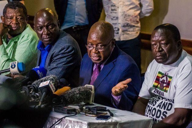 Leader of the Zimbabwe's War Veterans Association Christopher Mutsvangwa (centre) speaks during a press...