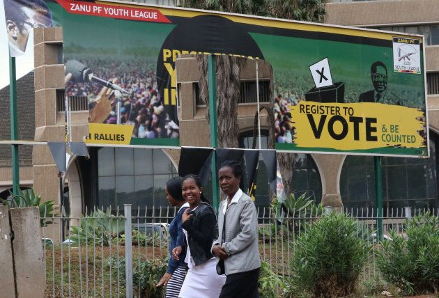 People walk past torn billboards of Zimbabwean President Robert Mugabe's Zimbabwe African National Union...
