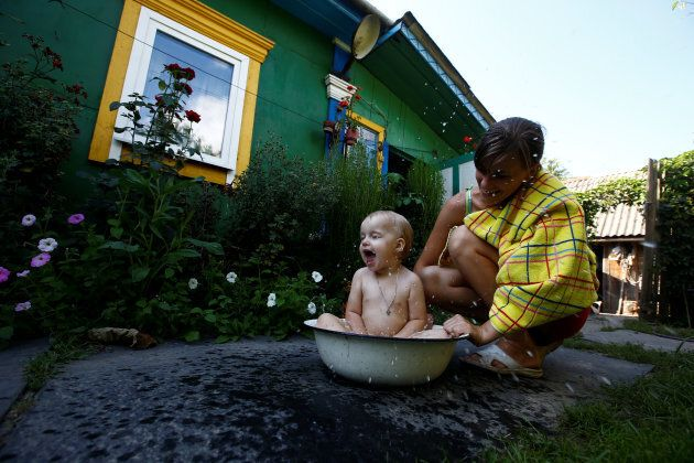Ekaterina, a granddaughter of 75-year old Ekaterina Panchenya, bathes her daughter Dasha in a basin on a hot summer day in the village of Pogost, Belarus.