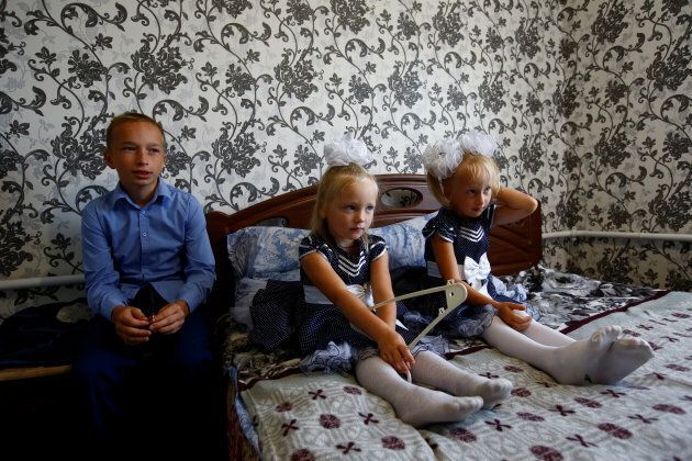 Oleg (L), Lada and Ulyana Skidan sit at their home before Oleg goes to classes on the first day of school in the village of Khrapkovo, Belarus.