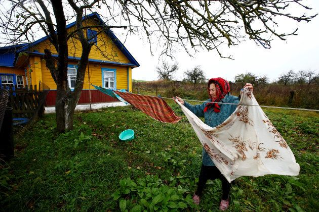 Valentina Zhih, 77, hangs linen on the washing line at her house in the village of Danilovichi, Belarus.