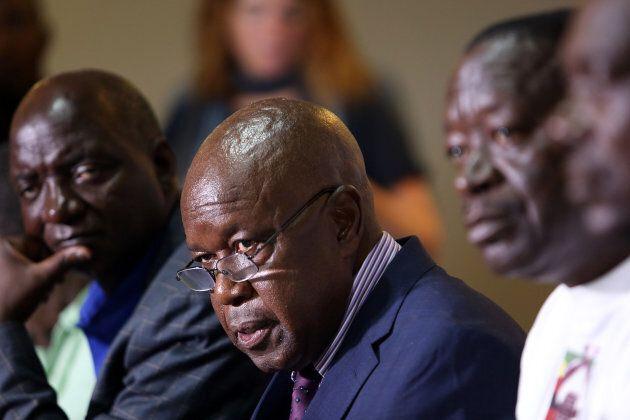 Chris Mutsvangwa, center, head of the Zimbabwe War Veterans Association, speaks during a news conference...