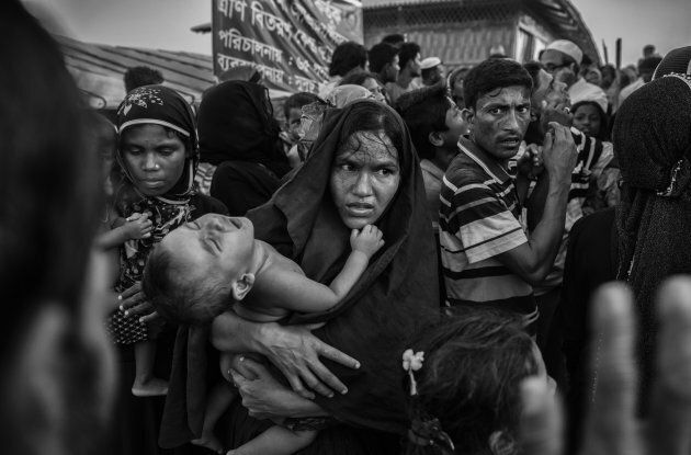 A Rohingya refugee woman struggles in the crowd at the Kutupalong refugee camp near Cox's Bazar,