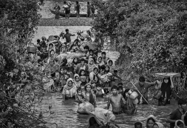 Rohingya Muslim refugees crowd a canal as they flee over the border from Myanmar into Bangladesh at the...