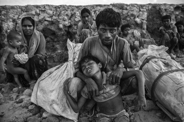 A Rohingya Muslim refugee boy is held by his father after arriving by boat to Shah Porir Dwip on October 30, 2017 near Cox's Bazar.