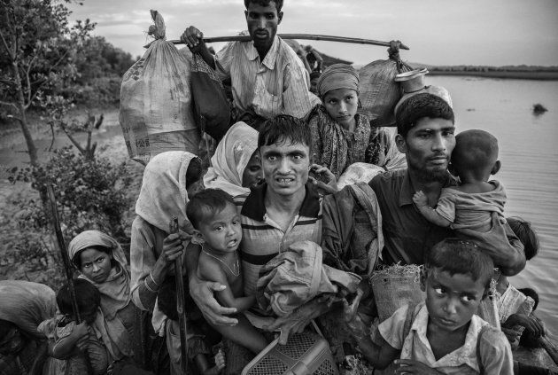 Rohingya Muslim refugees carry their belongings as they crowd on a berm while waiting to be allowed to...